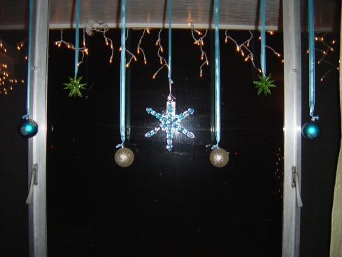 Ornaments in the window. I still have to replace the middle one...a couple of the gems fell out (that's what you get from Walmart!)