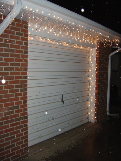 Our garage with the extra lights that we planned to put on the tree in our backyard but couldn't (the back door closes too tightly to run an extension cord through it).